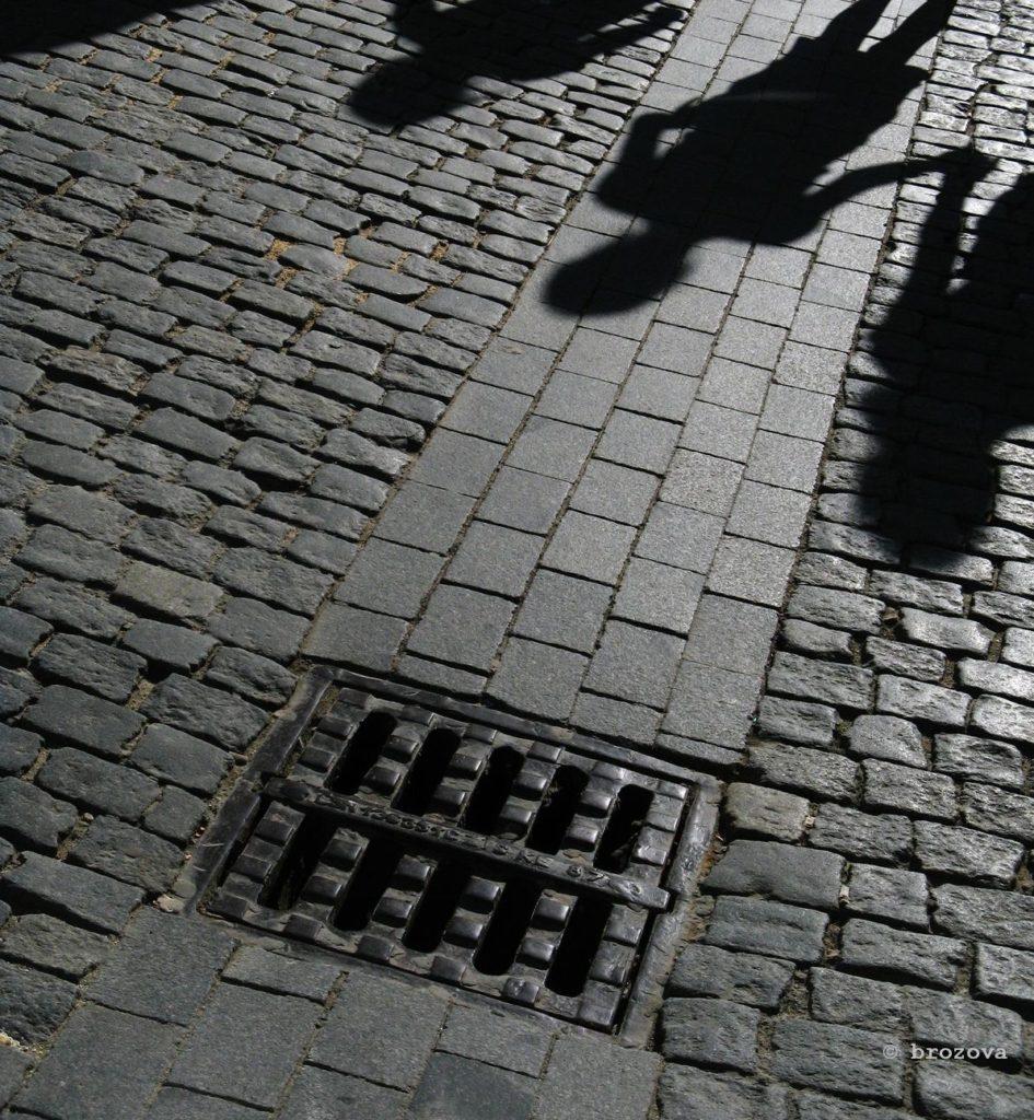 Shadows on street with drain
