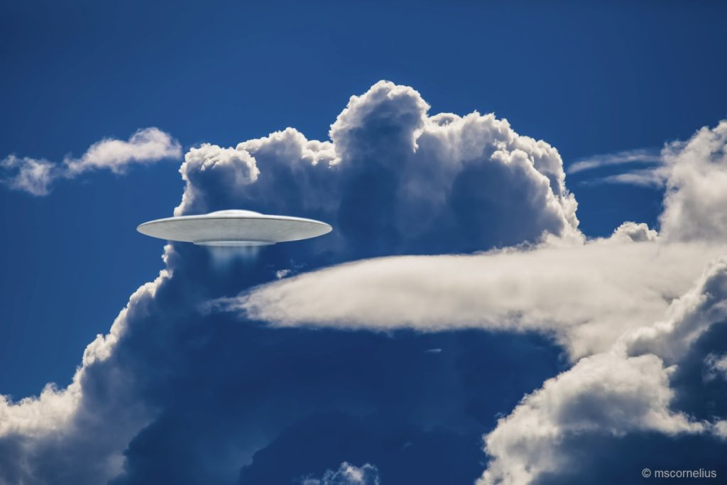 UFO spaceship in dramatic clouds with blue tones.