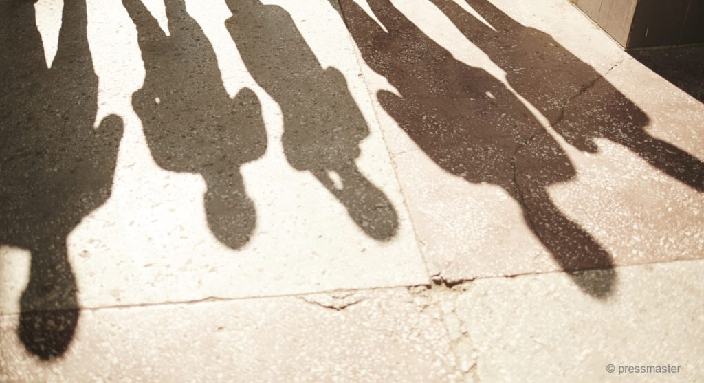 Shadows of five businesspeople standing outdoors,