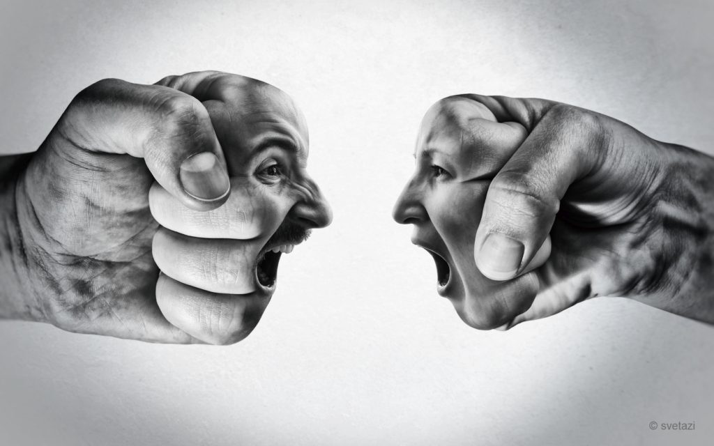 Two fists with a male and female face collide with each other on light background. Concept of confrontation, competition, family quarrel etc. Black and white.