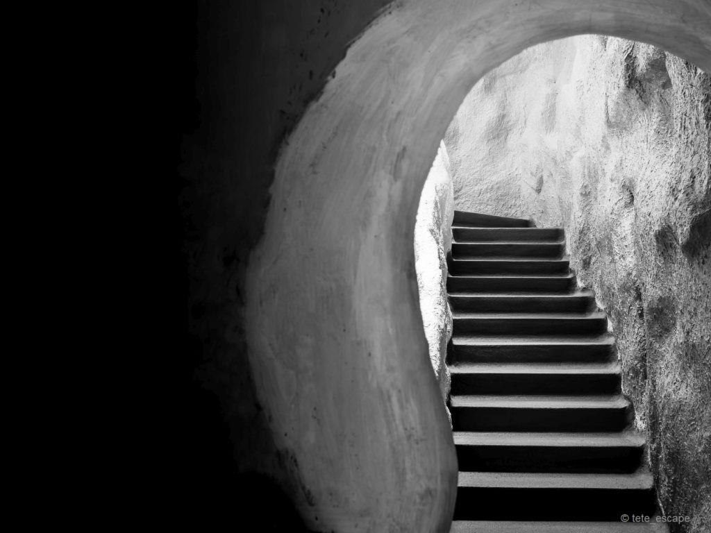 Stair from The Dark Room Cave Head Up to The Light of Exit in Black and White Style