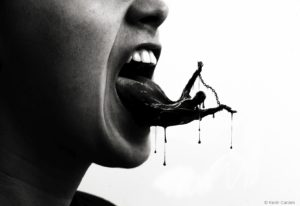 A person speaks and their tongue is covered in black filth.